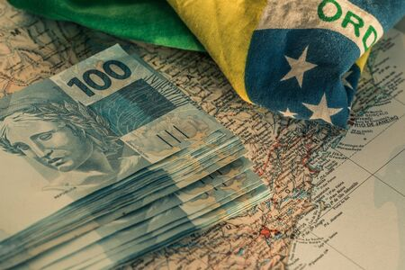 Brazilian money, 100 reais banknotes on the map of Brazil with a fragment of the national flag