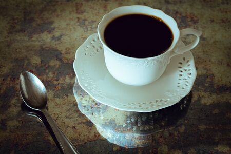 a cup of black coffee with a spoon in vintage style