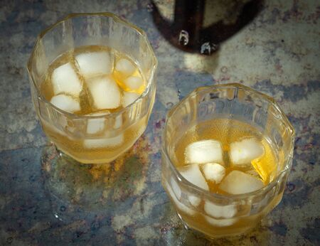 two glasses of whiskey with ice on a stylish counter