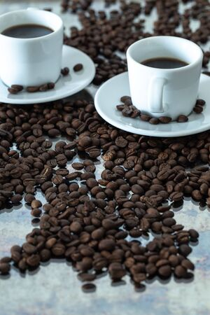 a cup of brewed coffee surrounded by whole unground beans