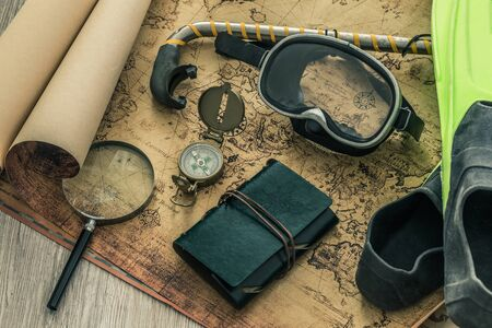 old map with a compass, notebook and diving equipment. The concept of searching for interesting diving sites or underwater treasures around the world.