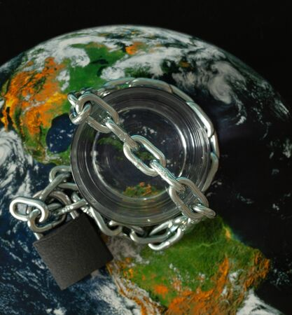 a glass of water wrapped in a chain and closed with a padlock. Globe as a background. The concept of the lack of drinking water in the world