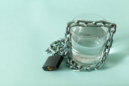 a glass of water wrapped in a chain and closed with a padlock. The concept of the problem of small drinking water resources in the world. Place for text