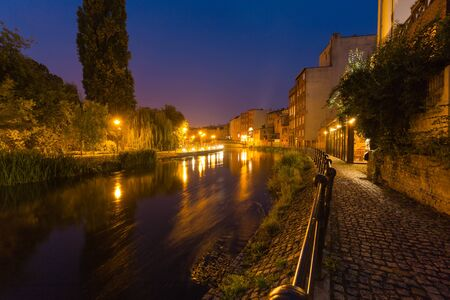 Bydgoszcz in Poland. Night view. Picturesque channels of the Brda River flowing through the city center. Old historic factory and residential buildings stand along the river 스톡 콘텐츠