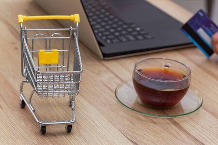 Compere su internet. Miniatura di un carrello della spesa con laptop, carta di credito e bicchiere di tè. Concetto. Fare la spesa comodamente senza uscire di casa