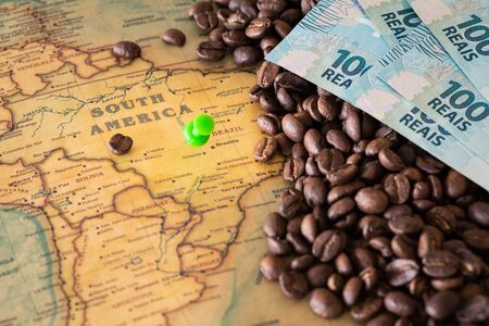 Old map of Brazil with scattered coffee beans and 100 reais banknotes, Concept of the largest coffee producer and exporter in the world