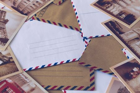 Stylish envelopes with space for an inscription and old cards from around the world. Travel and tourism concept Stockfoto