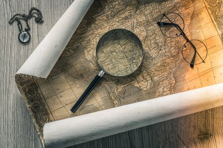 Old colonial map of South America with a magnifying glass, compass and period glasses. Vintage style Foto de archivo