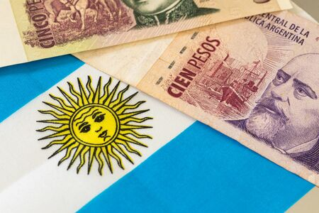 Argentinian banknotes of different value on the background of the flag of the country
