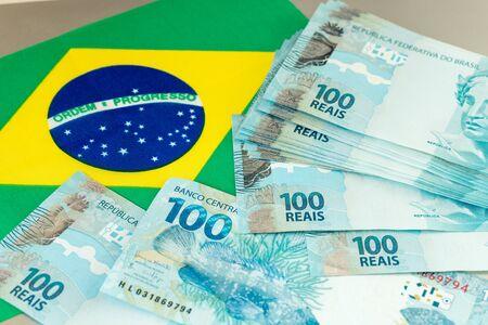 Brasilianische Geldbanknoten auf dem Hintergrund der Flagge des Landes