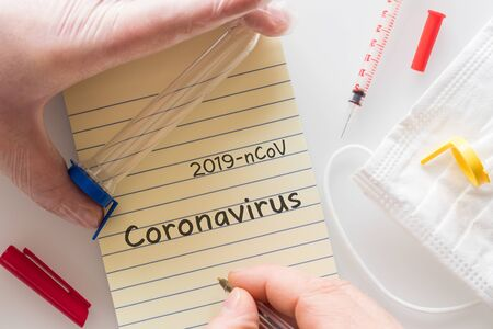 hand in a rubber glove holding a laboratory vial with the 2019-ConV virus. Concept, epidemiological threat, card with the inscription, Coronovirus, syringe, protective mask