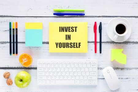 A workplace with a large inscription, Invest in Yourself. The concept of personal or business development and self-fulfillment. Keyboard, pens, healthy snacks Stock Photo