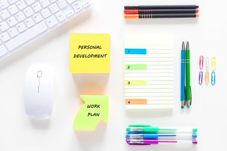 workplace, office. Handwritten note Personal development Below the arrow with the text Work plan Notebook with space for your own inscription, keyboard, pens, staplers
