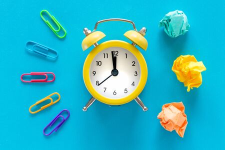small yellow alarm clock on blue background, Colorful office staples and crumpled paper balls. Top View. The concept of office work, business and advertising