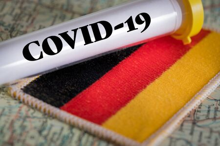 test tube with a positive Coronavirus test against the German flag