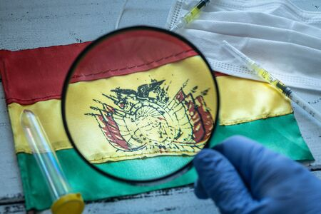 hand in a protective glove holding a magnifying glass over the flag of Bolivia, Coronavirus tubes, anti-virus masks. The concept of the spread of the epidemic and its impact on the country