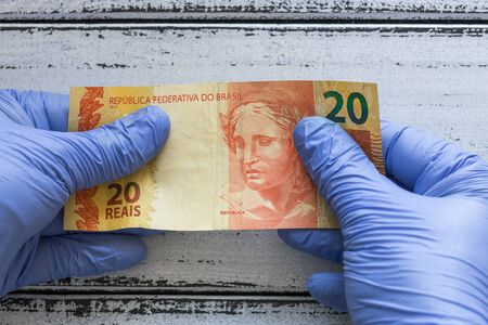 Brazilian money, Twenty reais kept in rubber gloves. The concept of economy and financial threats during the Coronavirus pandemic Zdjęcie Seryjne