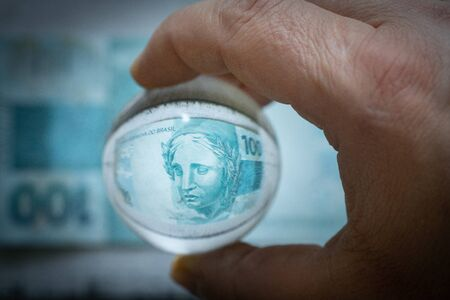 A Brazilian Reais 100 banknote reflected in a glass sphere. The concept of uncertain economy and financial