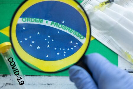 hand in a protective glove holding a magnifying glass over the flag of Brazil, Coronavirus tubes, anti-virus masks. The concept of the spread of the epidemic and its impact on the country Zdjęcie Seryjne