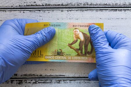 Costa Rica, five Colones banknote kept in rubber gloves. The concept of economy and financial threats during the Coronavirus pandemic Zdjęcie Seryjne