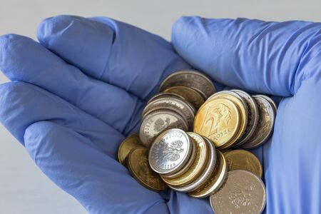 hand in a rubber glove with coins. Polish money, The concept of inflation caused by the coronavirus epidemic