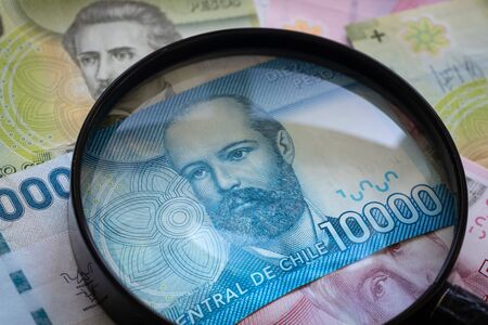 Chile money, various banknotes under the magnifying glass. The concept of changing rates and their impact on the economy Stock Photo