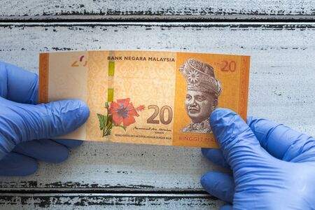 Malay money, twenty ringgit banknote kept in rubber gloves. The concept of economy and financial threats during the Coronavirus pandemic Zdjęcie Seryjne