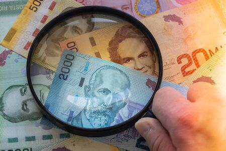 Costa Rica money, various banknotes under the magnifying glass. The concept of changing rates and their impact on the economy