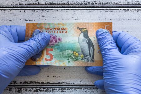 New Zealand five Dollar banknote kept in rubber gloves. The concept of economy and financial threats during the Coronavirus pandemic