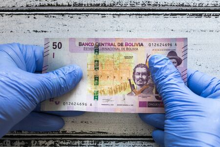 Bolivian money, 50 bolivianos kept in rubber gloves. The concept of economy and financial threats during the Coronavirus pandemic Zdjęcie Seryjne