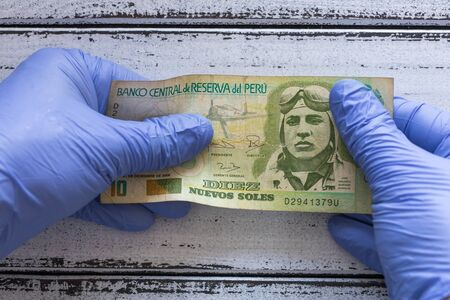 Peru money, ten Soles banknote kept in rubber gloves. The concept of economy and financial threats during the Coronavirus pandemic