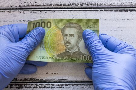 Chile money, Banknote kept in rubber gloves. The concept of economy and financial threats during the Coronavirus pandemic Stock Photo