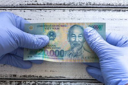 Vietnam money, Dong, banknote kept in rubber gloves. The concept of economy and financial threats during the Coronavirus pandemic