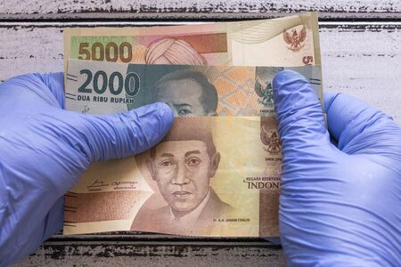 Indonesian money, banknotes kept in rubber gloves. The concept of economy and financial threats during the Coronavirus pandemic Zdjęcie Seryjne