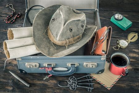 Preparing for travel. Packing the suitcase. Adventure concept. Retro style. Old maps, suitcase, notebook, magnifier, flashlight, combo hat, compass, cup of tea on a wooden table Zdjęcie Seryjne