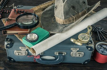 Preparing for travel. Great adventure planning concept. Retro style. Old maps, expedition accessories. suitcase, notebook, magnifier, flashlight, compass, tea cup, hat on a wooden bench