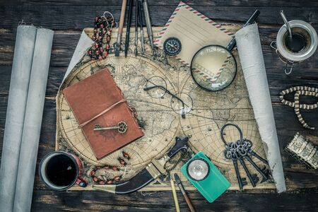 Preparing for travel. Great adventure planning concept. Retro style. Old maps, expedition accessories. Notebook, magnifier, flashlight, compass, tea cup, treasure chest and key on a wooden bench