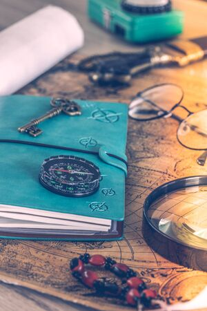 Travel notebook lying on an old map with old glasses, a flashlight, expedition accessories, Retro style. Expedition planning concept