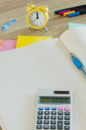 An open notebook with space for text. Alarm clock set at five to twelve, calculator, colored cards, pens. Office concept