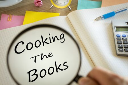 Magnifying glass writing 'Cooking the books' in a notebook. Creative accounting concept. Calculator, office accessories, clock Zdjęcie Seryjne