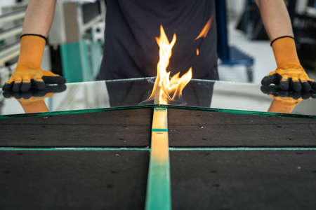 Glazier cuts safety glass, VSG (Very Safe Glass) The fire burns through the foil connecting the panes, A specialized technique of cutting laminated glass