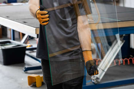 Glass factory, Worker carrying glass panes