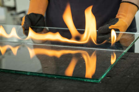 Glazier cuts safety glass, VSG (Very Safe Glass) The fire burns through the foil connecting the panes, A specialized technique of cutting laminated glass Фото со стока