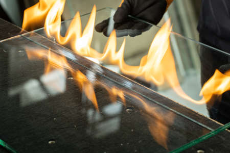 Glazier cuts safety glass, VSG (Very Safe Glass) The fire burns through the foil connecting the panes, A specialized technique of cutting laminated glass 免版税图像