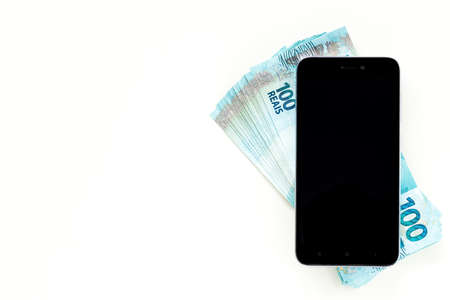 Smartphone and Brazilian currency, Reais, White background, Blank space for text 免版税图像