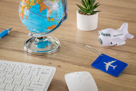 Desk with aviation and travel items. Globe, toy plane, Luggage tag, Computer keyboard, Air travel planning concept