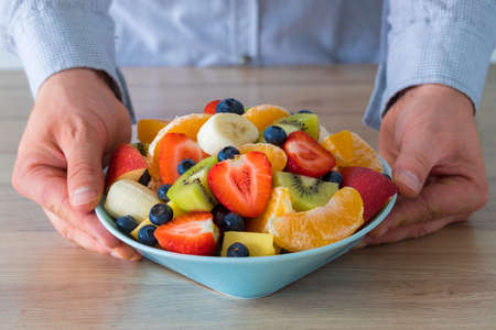 Fresh Fruit Salad, The man holds a plate full of sliced fruit over the table
