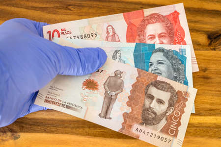 Columbian money, pesos banknotes kept in rubber gloves. The concept of economy and financial threats during the Coronavirus epidemic