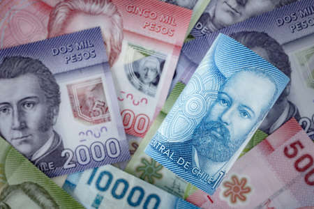 Chile Money, Ten thousand peso rolled up, lying in the background of other banknotes of this country