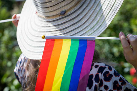 A woman in a stylish summer hat with a flag supporting the LGBT movement on her shoulder Reklamní fotografie